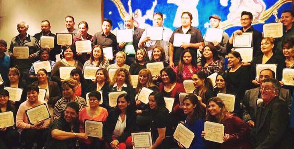Immigrant entrepreneurs holding up their certificates for the Emprendedores program