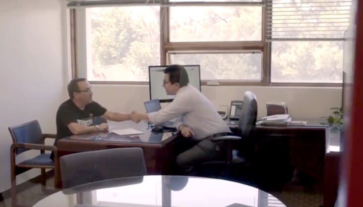 Josue speaking with someone at a desk